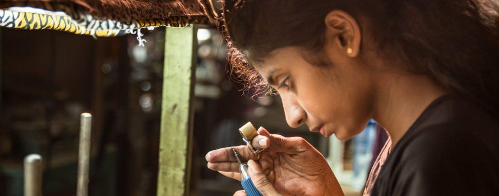 Mädchen schleift und untersucht einen Saphir Farbedelstein